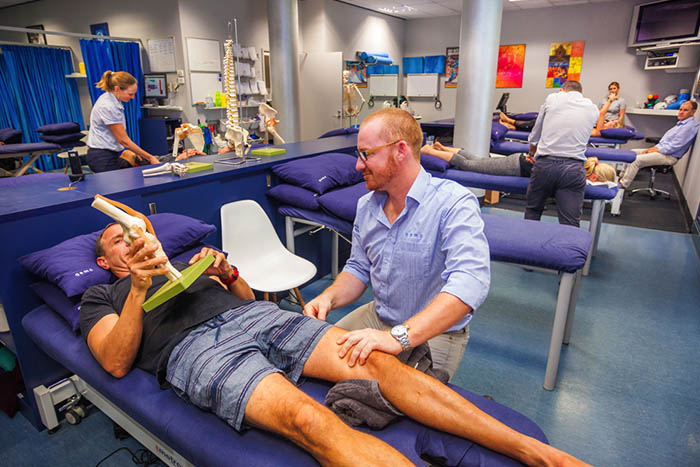 Sports physiotherapist showing his patient a demo
