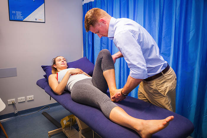 Male physician performing stretches on a female patient