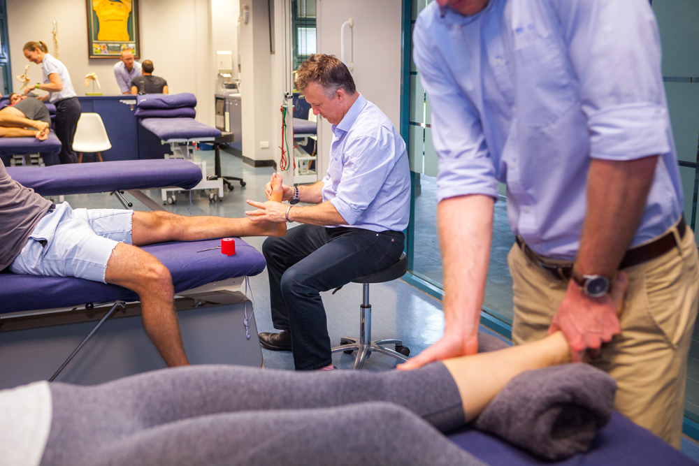 Two male physicians treating their patients at a Brisbane based physiotherapy clinic