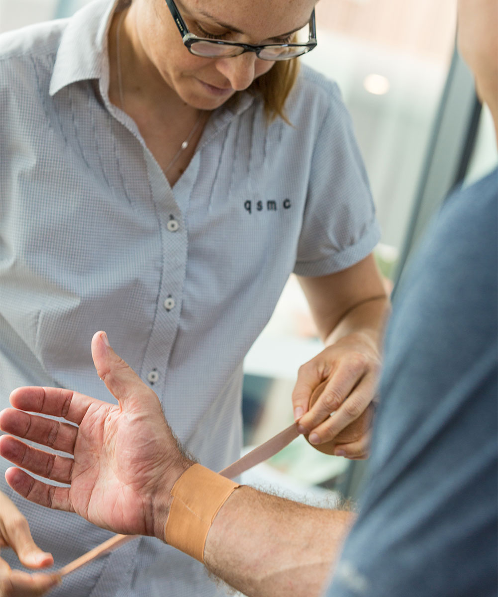 Female Brisbane Physiotherapist using tape to strap and secure a wrist